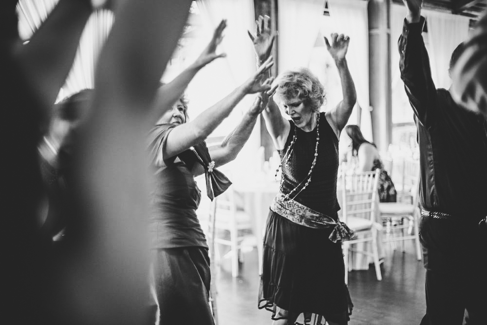 san   diego wedding photographer | monotone shot of middle aged women dancing with   arms up