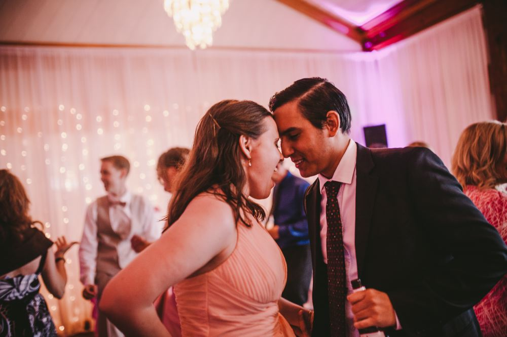 san   diego wedding photographer | man with hair parted holding wine bottle dancing   with woman in peach dress