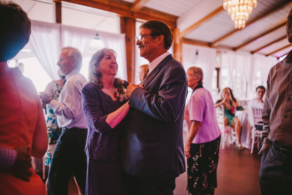 san   diego wedding photographer | middle aged man and woman in dark formal outfits   dancing