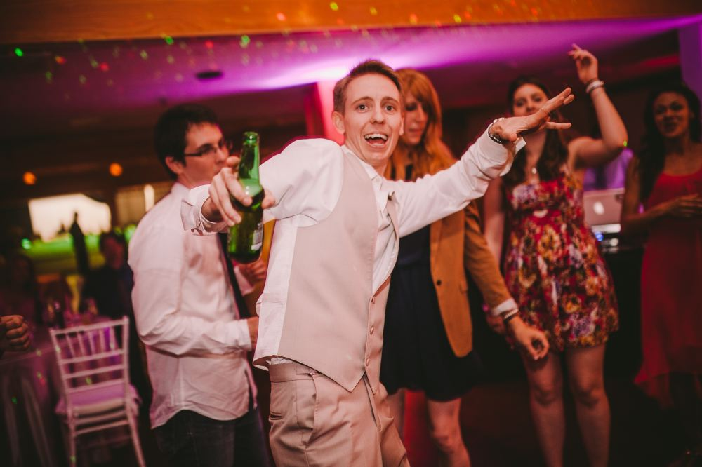 san   diego wedding photographer | man in beige vest dancing holding bottle of beer