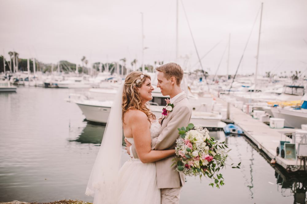 san   diego wedding photographer | man holding woman with bouquet in front of docks