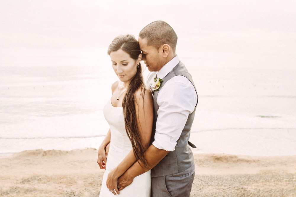 san   diego wedding photographer | groom holding bride from behind with beachscape   in background