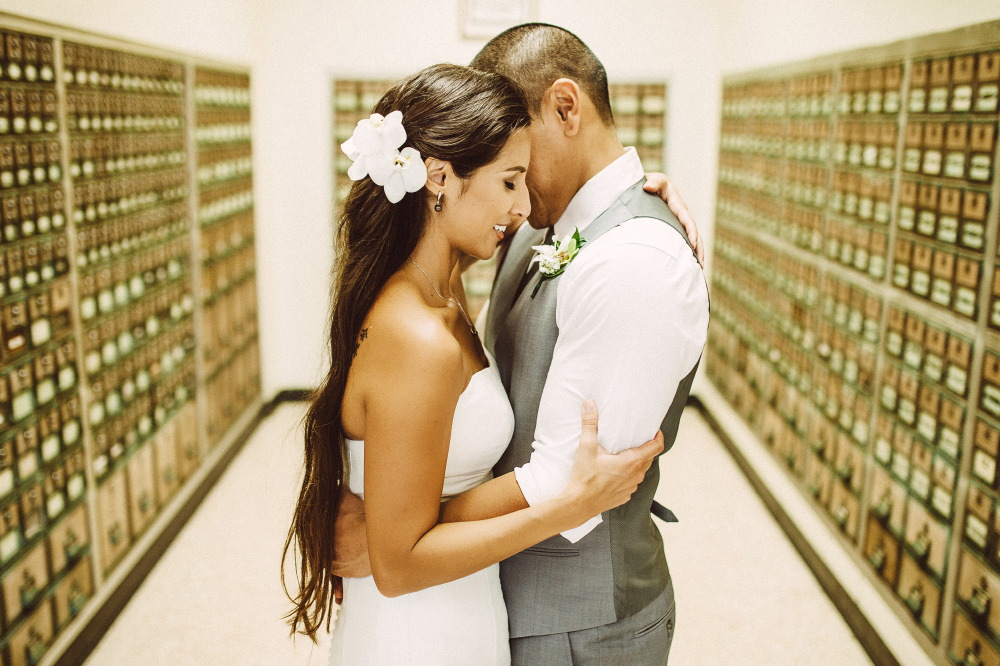 san   diego wedding photographer | bride and groom in grey vest holding each other   close in middle of white room