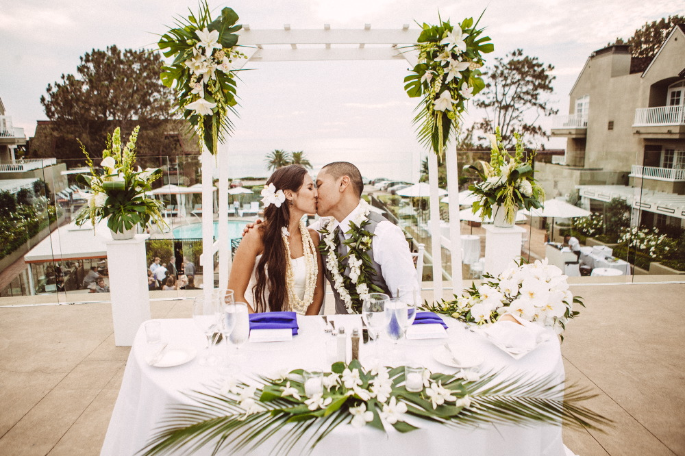 san   diego wedding photographer | newly wed couple with lay around their neck   sitting kissing