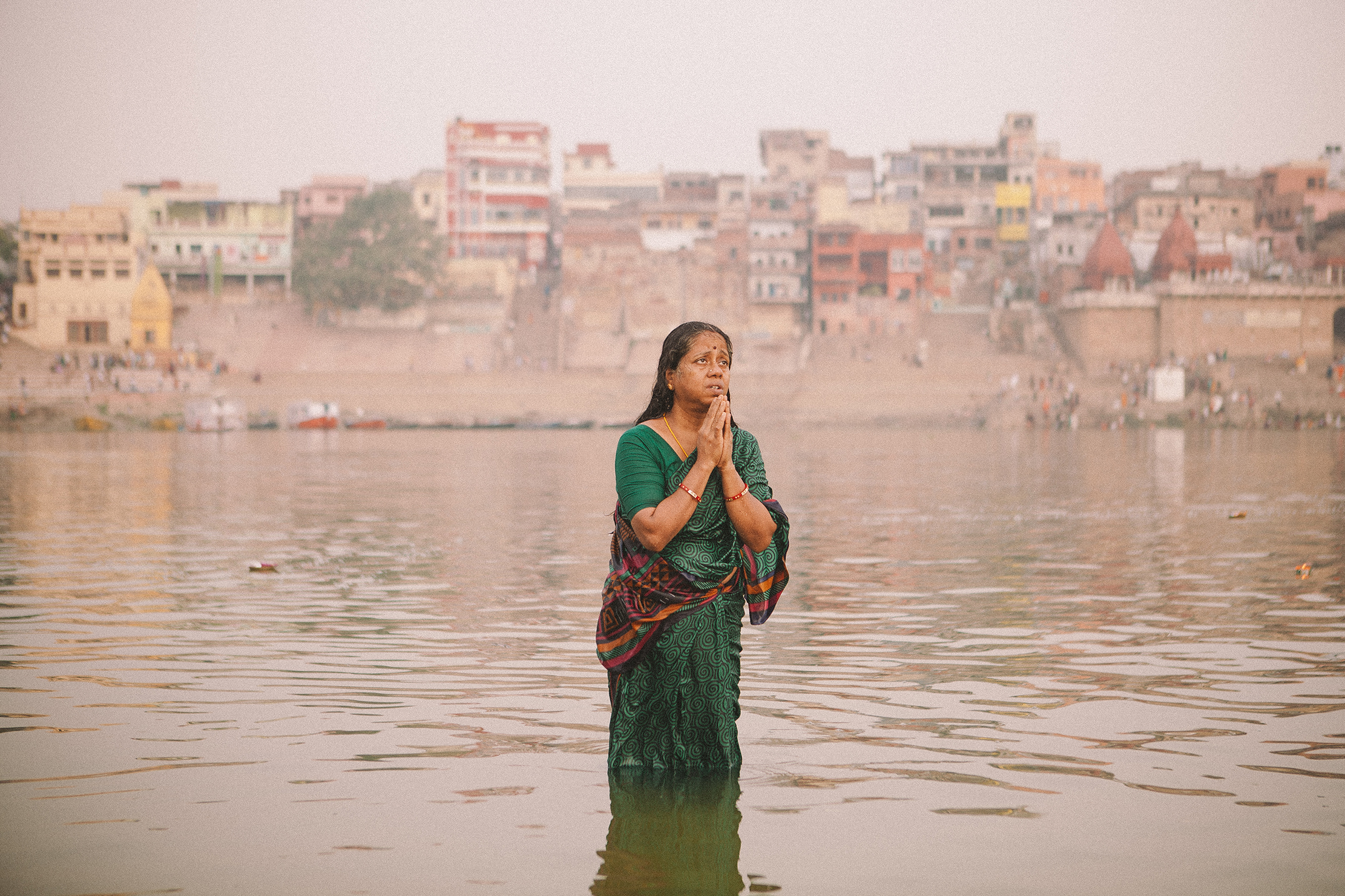 A devotee starts her day by bathing and intimately praying in the Ganga river, Hindu religion believes that the river possesses religious power that washes away impurities and brings them closer to their ancestors and to god.  Varanasi, India 2014