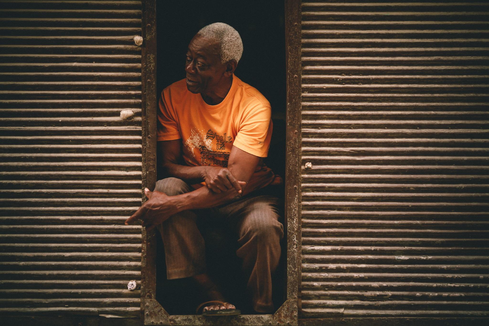 san diego wedding   photographer | man with graying hair in orange shirt standing in metal gate