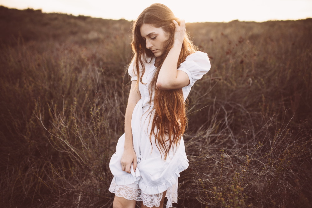 san diego wedding   photographer | long-haired brunette woman in white dress with hand tucking   her hair behind ear on field