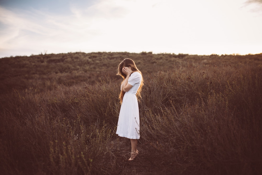 san diego wedding   photographer | side view of long-haired brunette barefoot woman tiptoeing on   field and covering face