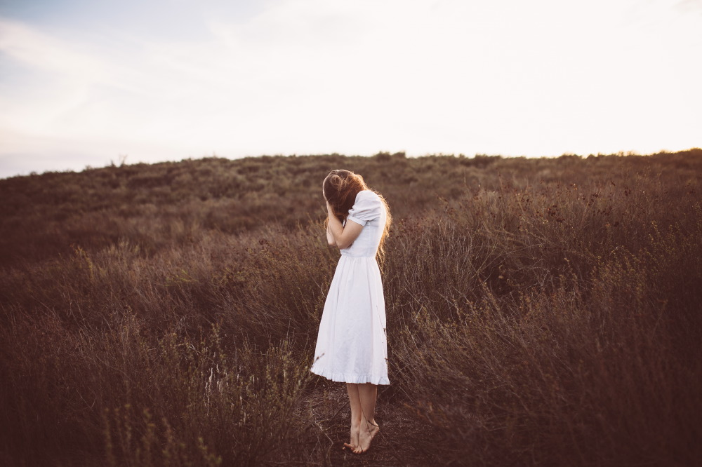 san diego wedding   photographer | long-haired brunette woman tiptoeing barefoot on field and   covering face