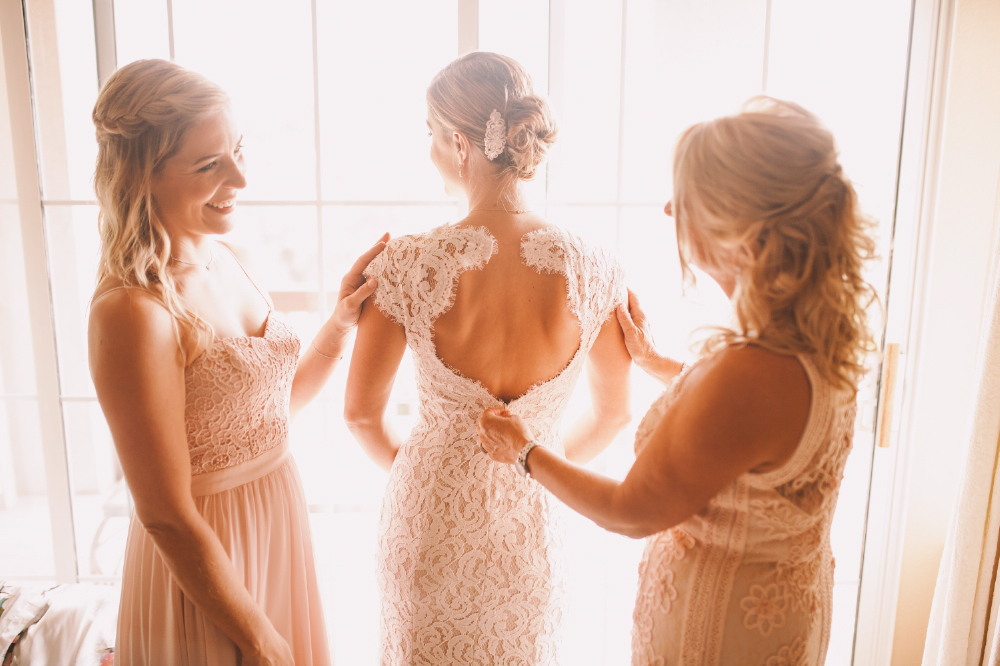 san diego wedding   photographer | bride's back being fixed with bridesmaids smiling