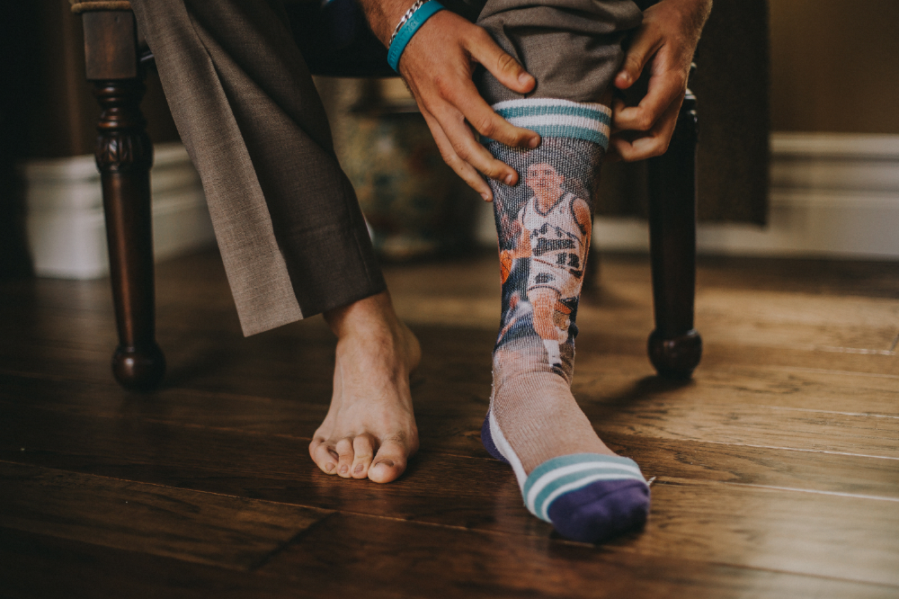 san diego wedding   photographer | man putting on socks with basketball player on it