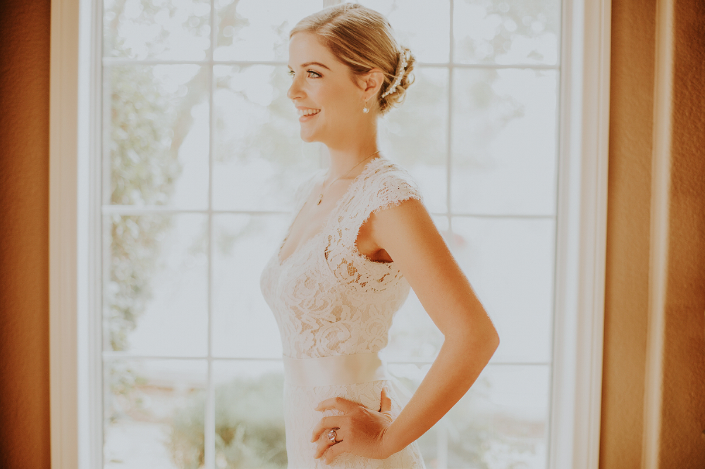 san diego wedding   photographer | woman in white dress smiling in front of window illuminated   with sun