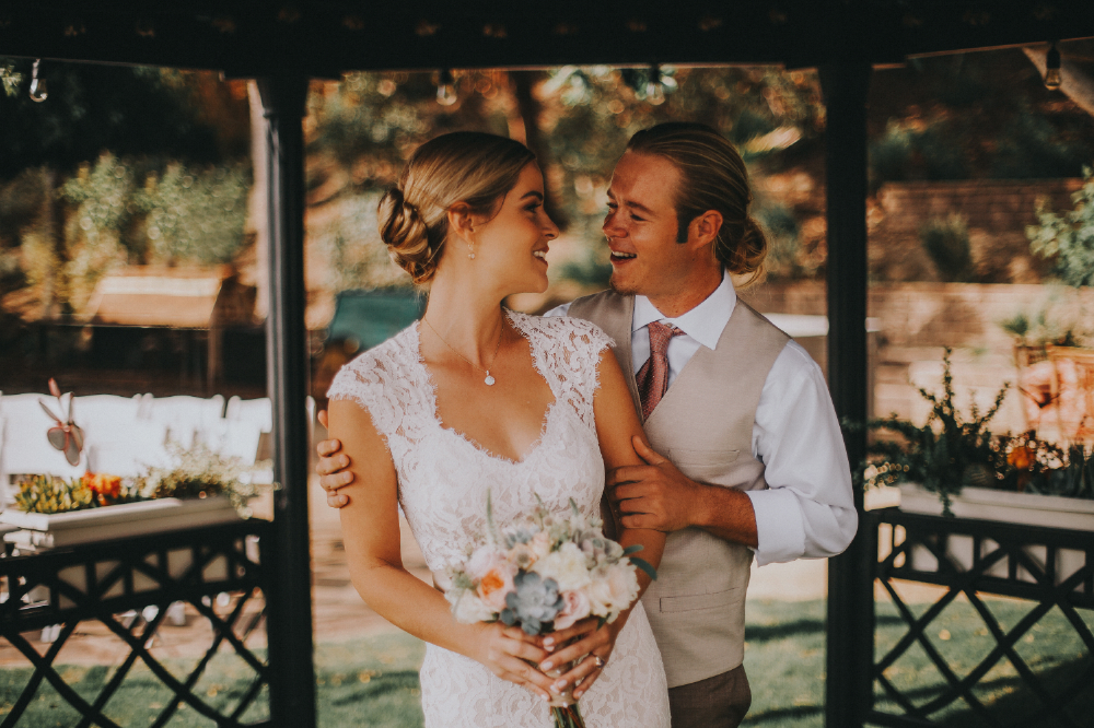 san diego wedding   photographer | woman looking behind her with groom holding her arms