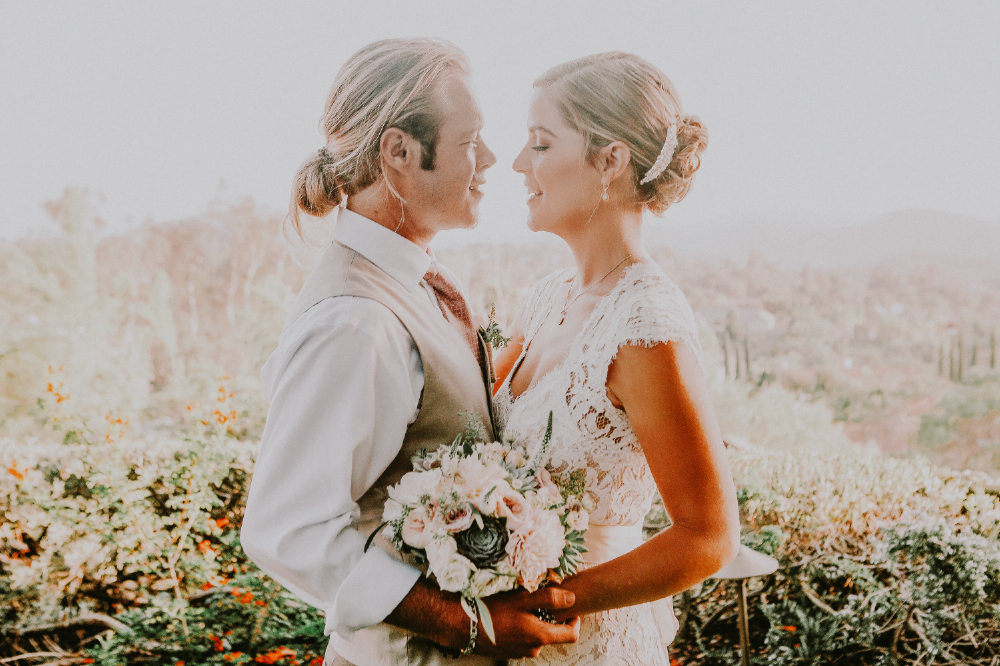 san diego wedding   photographer | bride and groom with bouquet between them with garden in   background blurred