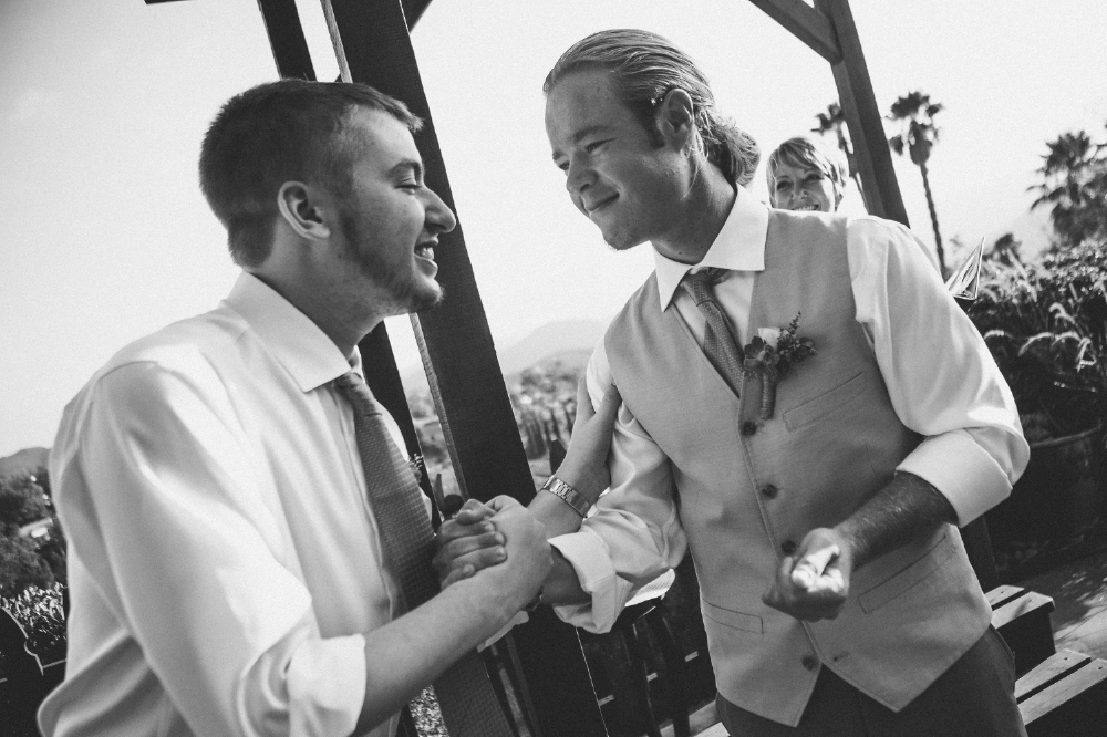 san diego wedding   photographer | groom holding groomsman's hand smiling