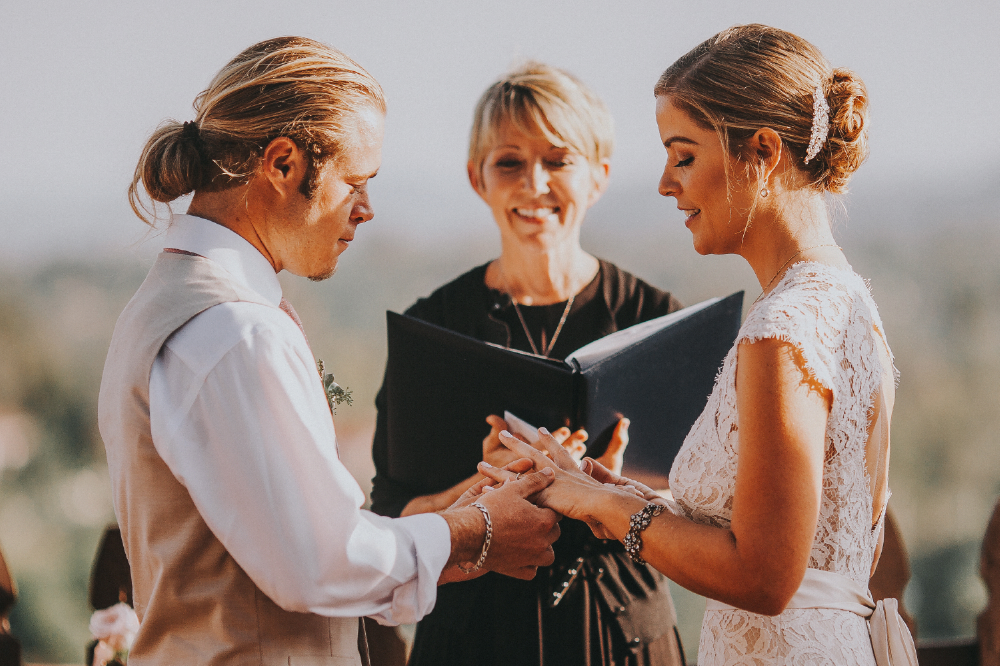 san diego wedding   photographer | groom putting on ring on bride in front of smiling officiator