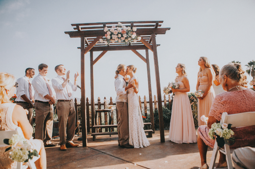 san diego wedding   photographer | bride and groom kissing with bridesmaids and groomsmen around   them