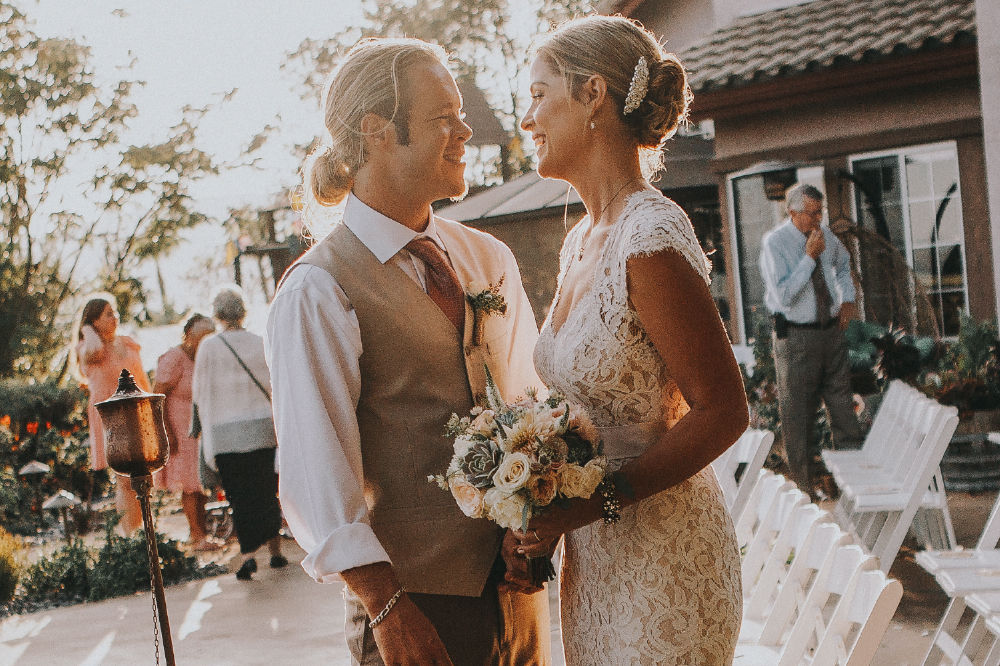 san diego wedding   photographer | bride with bouquet smiling at groom with chairs behind them