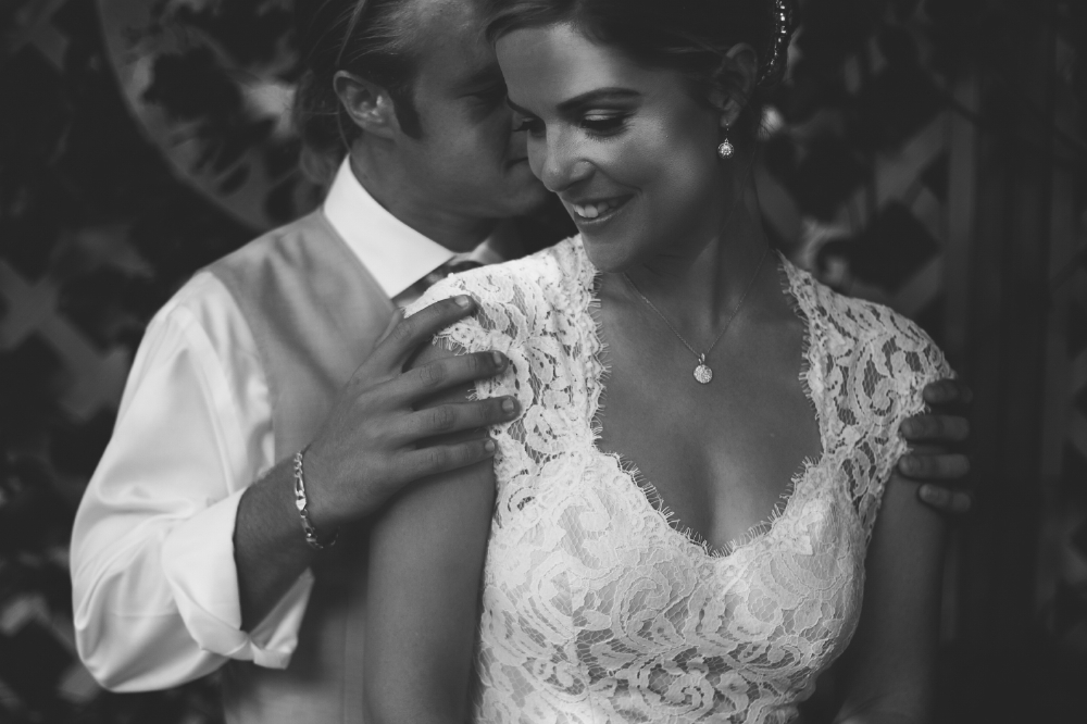 san diego wedding   photographer | monotone shot of groom holding bride's shoulders from behind   in front of cross fence