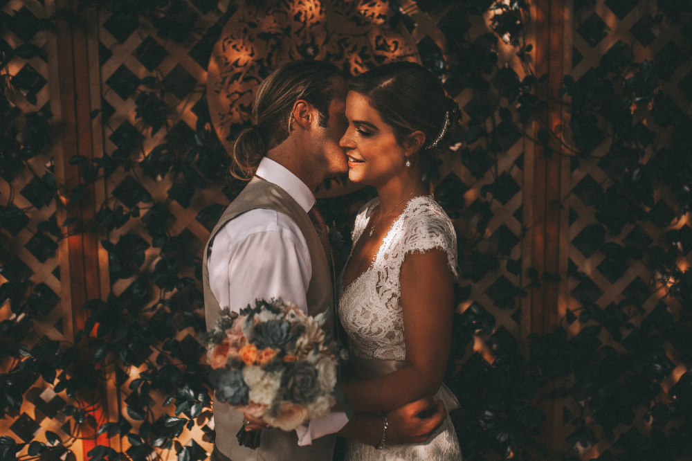 san diego wedding   photographer | bride holding bouquet and groom kissing bride's cheek in front   of wooden cross fence