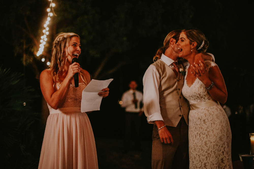 san diego wedding   photographer | groom kissing bride on cheek with guest saying something on   mic