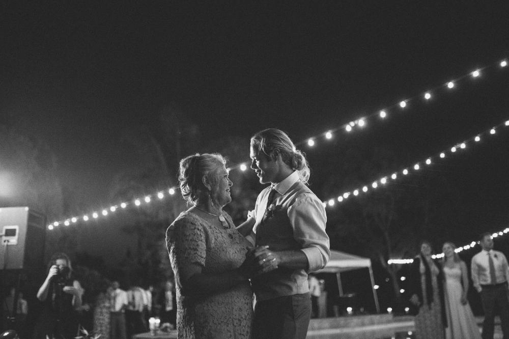 san diego wedding   photographer | monotone shot of groom dancing with old woman with lights   behind them