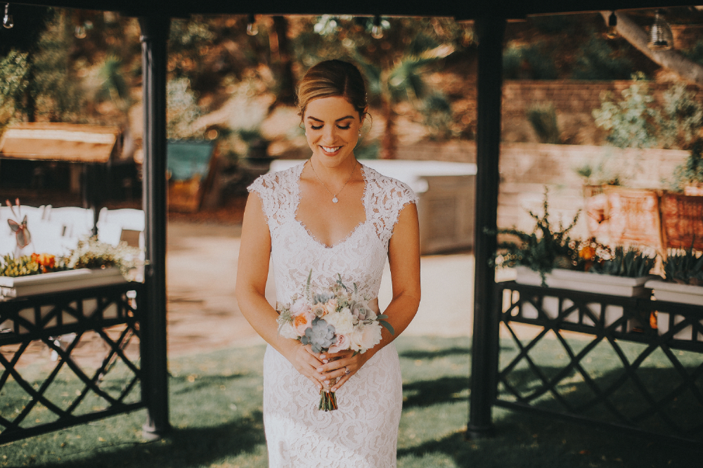 san diego wedding   photographer | woman in wedding dress holding bouquet looking down in gazebo