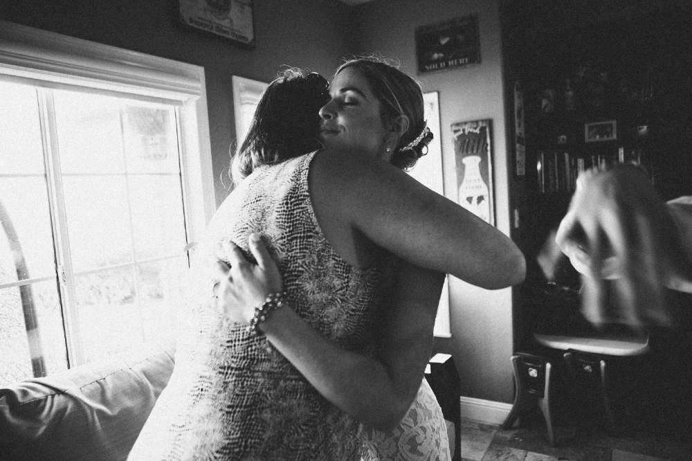 san diego wedding   photographer | monotone shot of bride hugging woman in dress with blurred   hand in shot