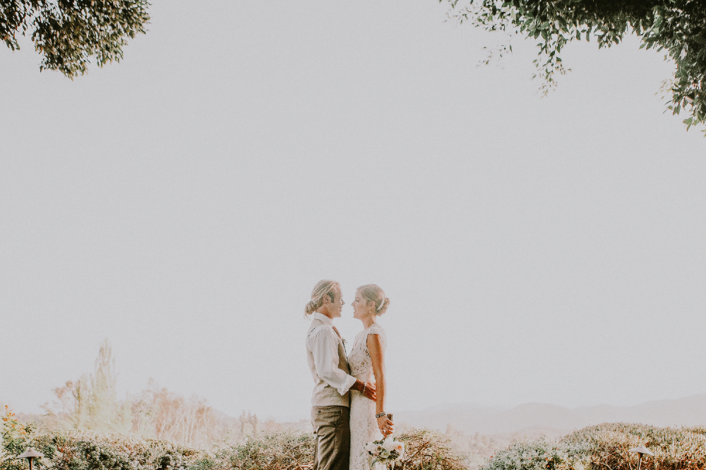 san diego wedding   photographer | exposed shot of groom and bride with groom holding bride's   waist with branches above them