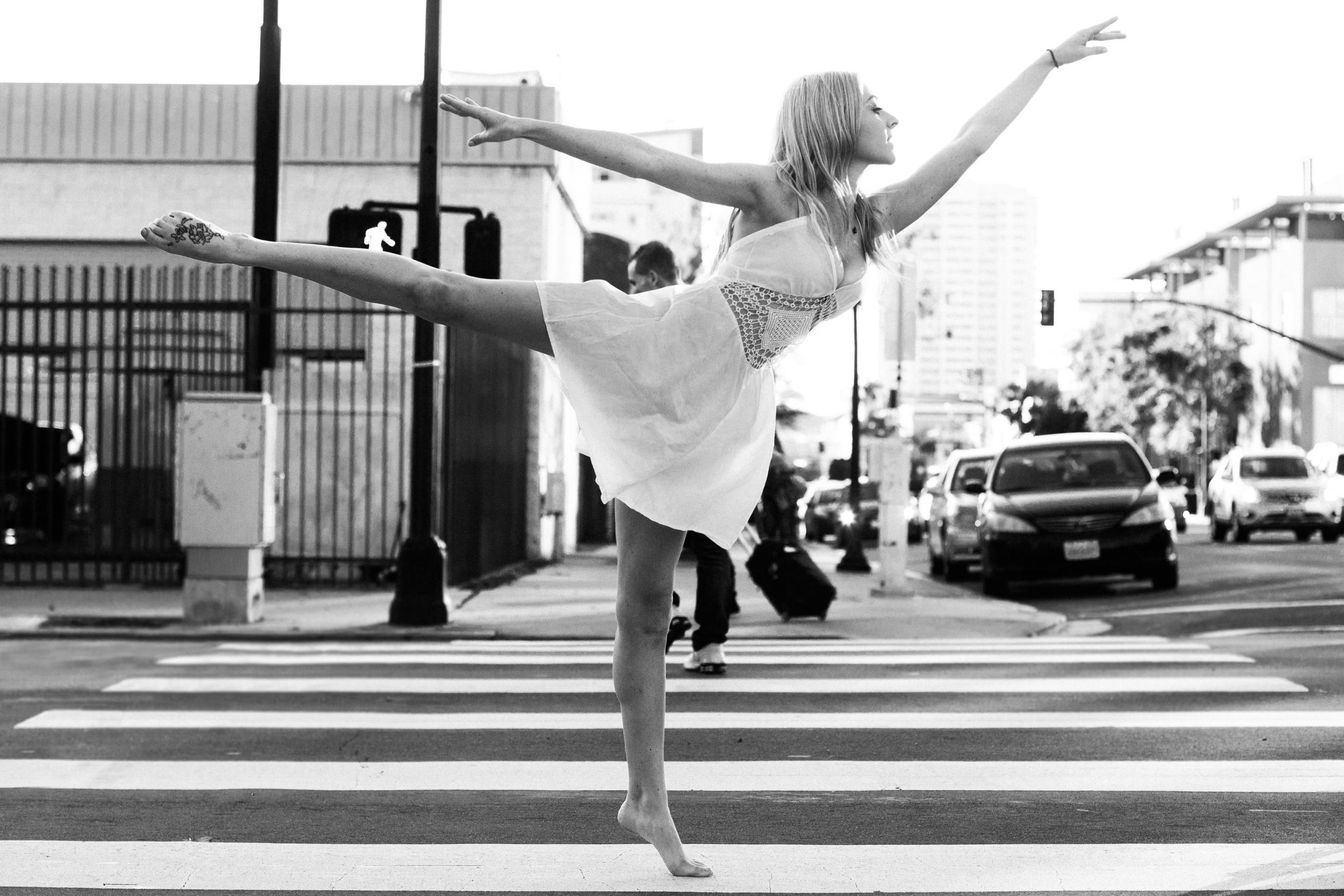 san diego wedding   photographer | monotone side view shot of barefoot blonde woman doing penche   on pedestrian lane