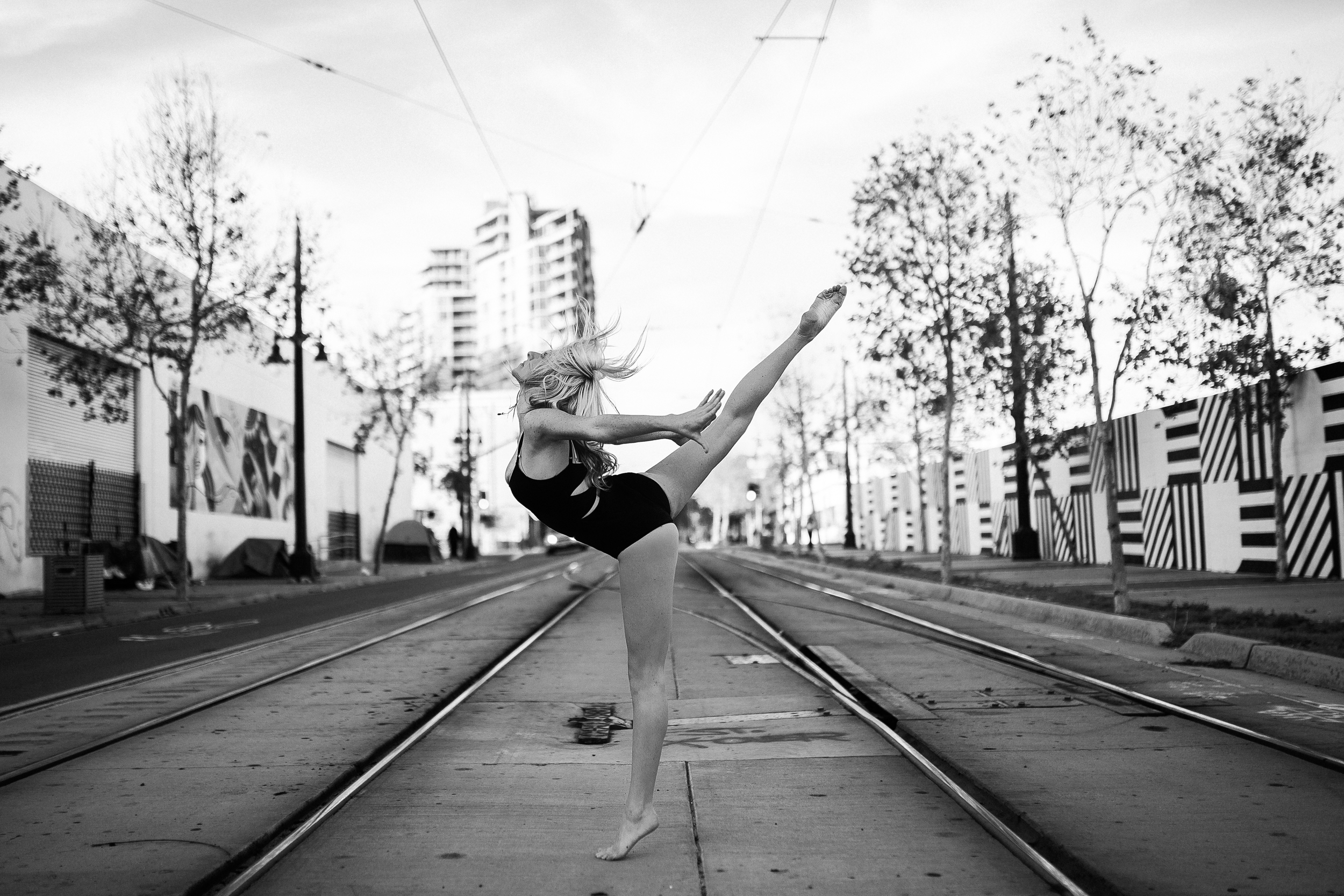 san diego wedding   photographer | monotone shot of barefoot blonde woman doing penche in middle   of street
