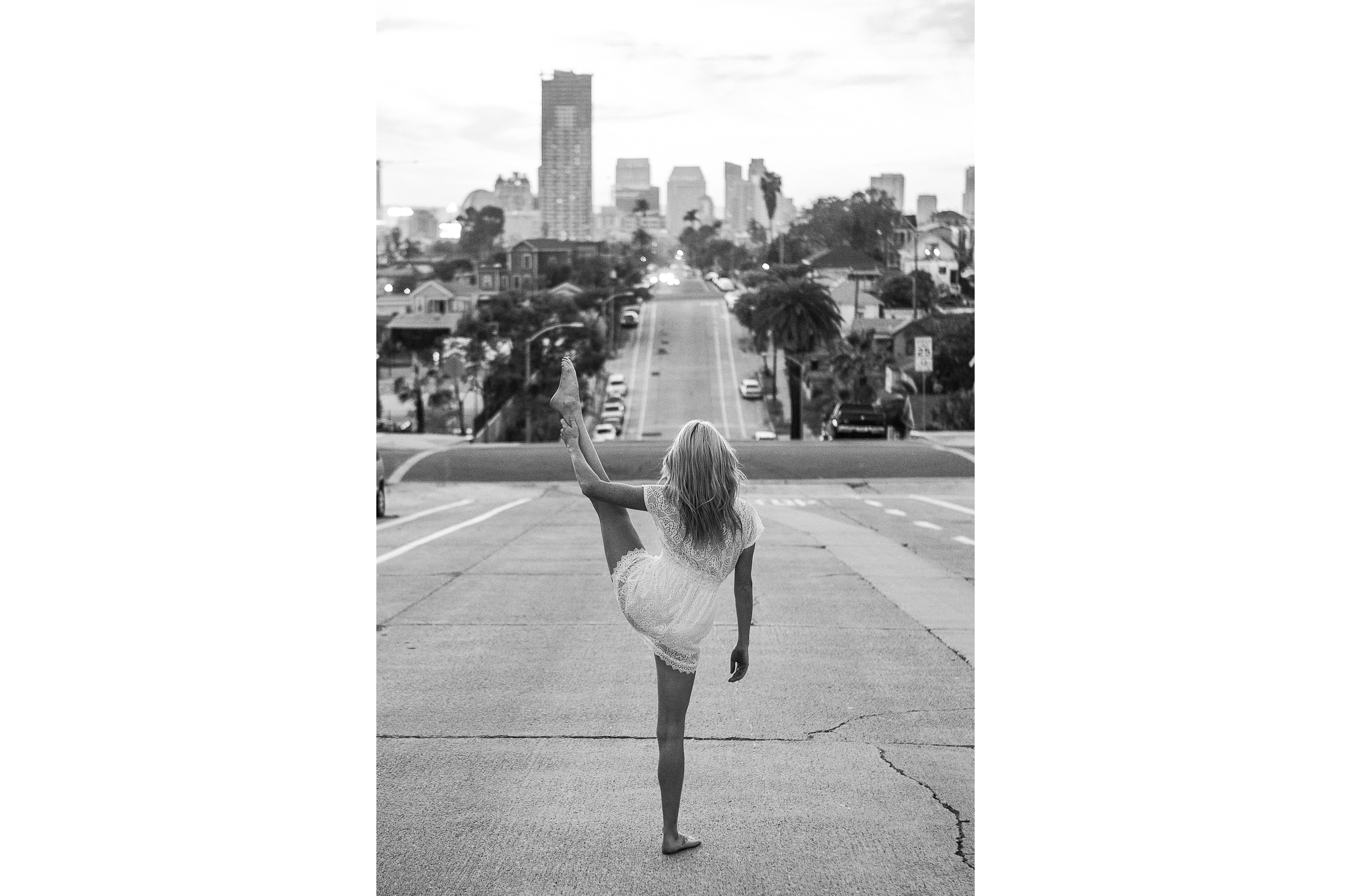 san diego wedding   photographer | monotone shot of back of blonde woman with one leg up in   middle of street
