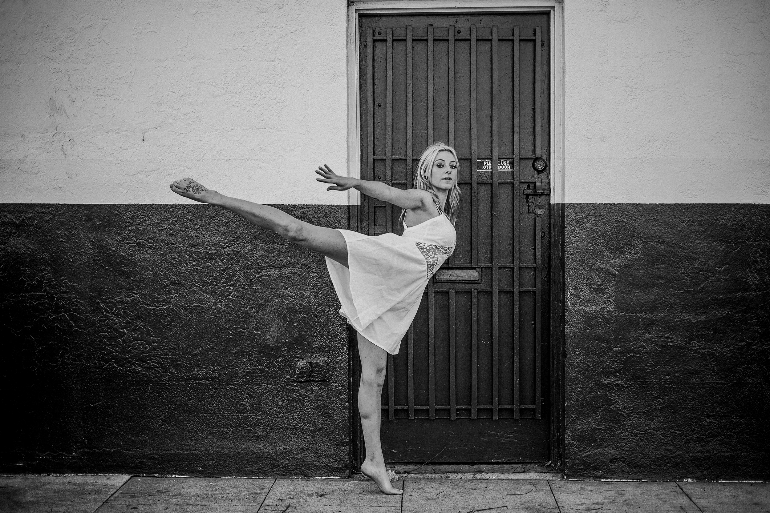 san diego wedding   photographer | monotone shot of barefoot blonde woman doing penche against   wall