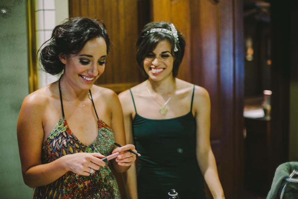 san diego wedding   photographer   women in tank tops looking at makeup