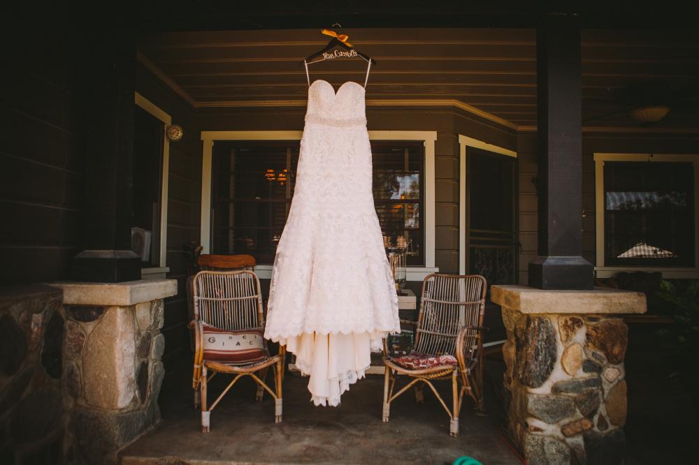 san diego wedding   photographer   wedding dress hanging from hanger on patio