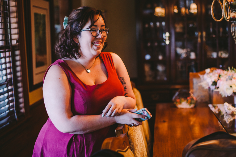 san diego wedding   photographer   woman in red ress and glasses leaning on chair smiling