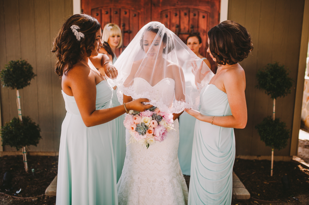 san diego wedding   photographer   bride under veil surrounded by bridesmaids in white dresses