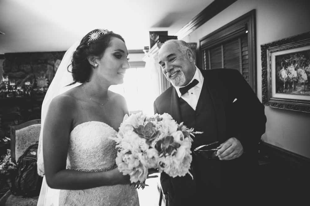 san diego wedding   photographer   monotone shot of bride in wedding dress holding bouquet of   flowers with man in black suit