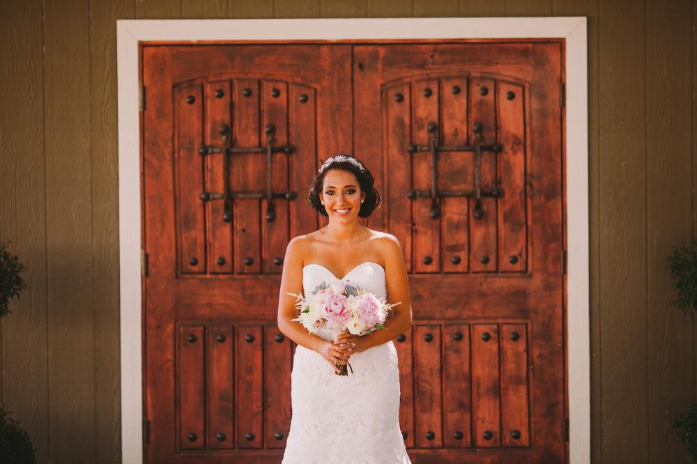san diego wedding   photographer   bride in wedding dress holding bouquet smiling standing in   front of door