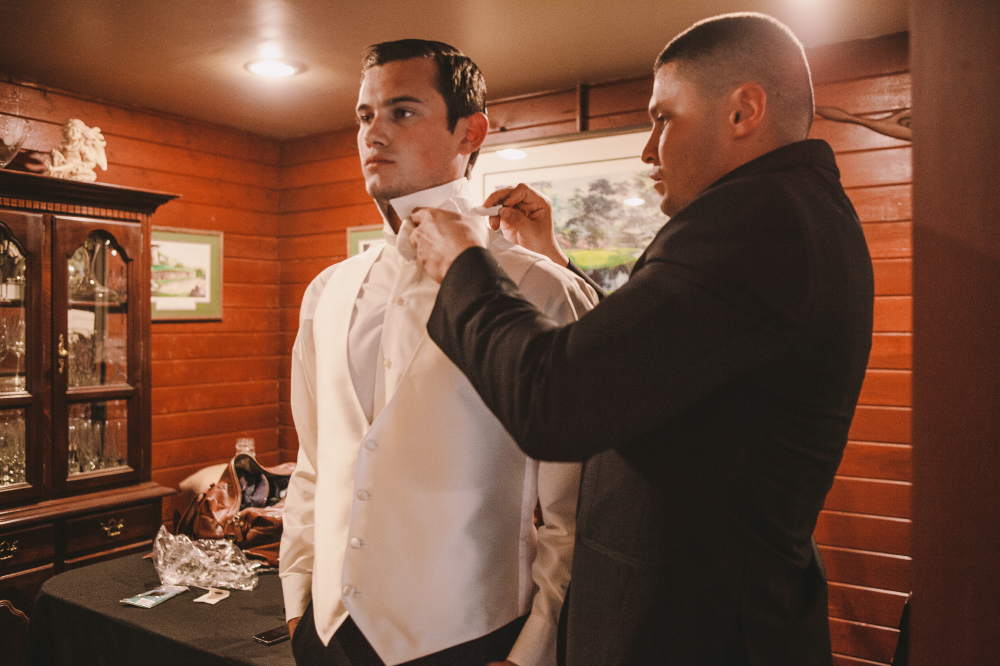 san diego wedding   photographer | man in black suit helping man in white vest get ready