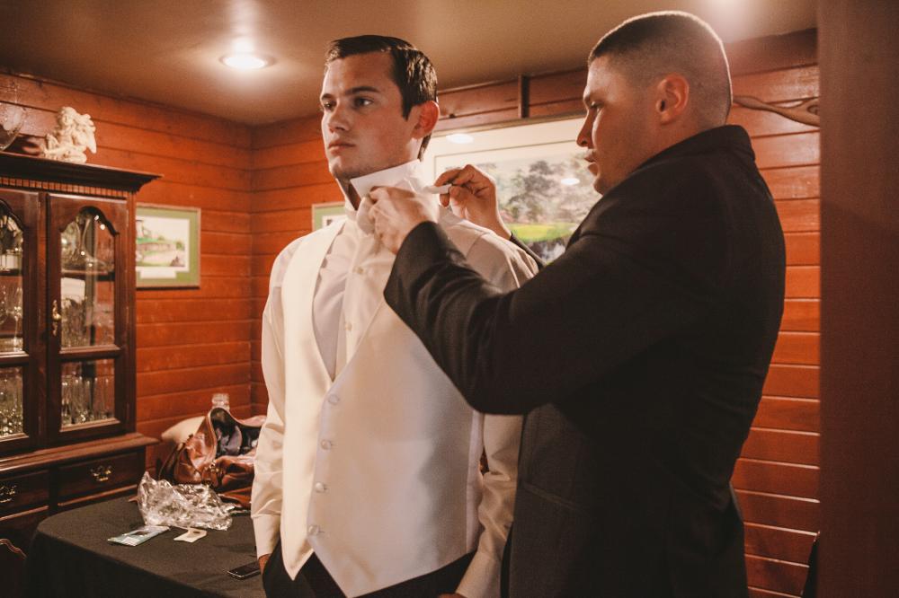 san diego wedding   photographer   man in black suit helping man in white vest get ready