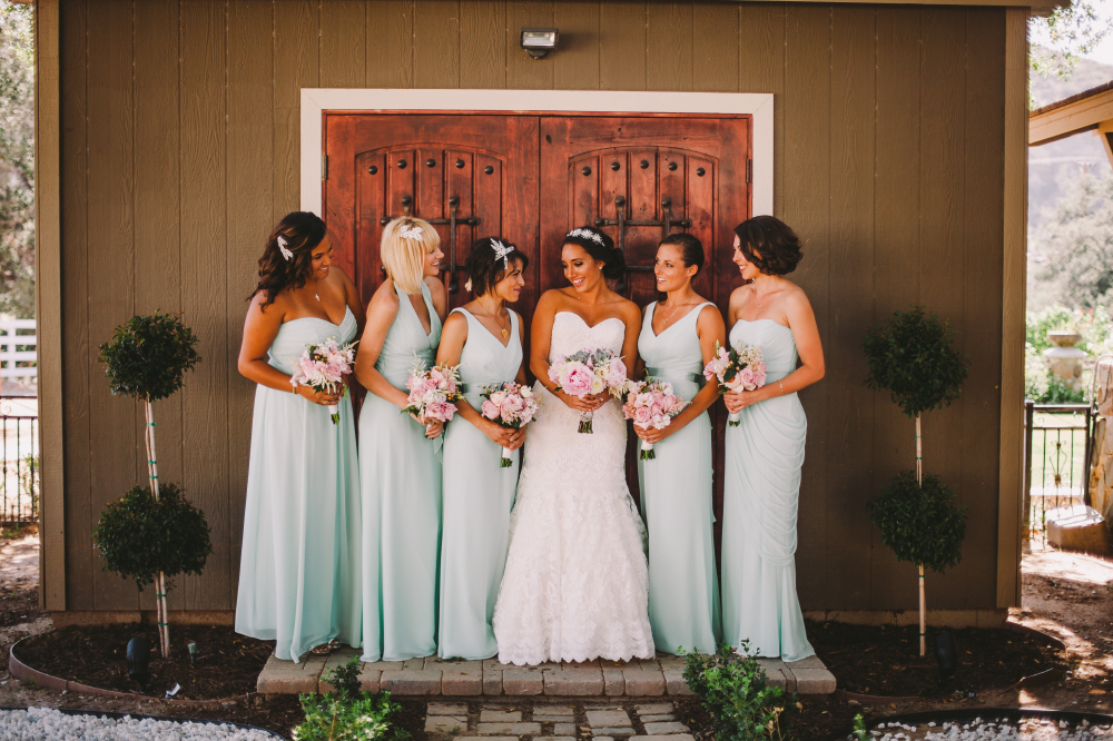 san diego wedding   photographer   bride and bridesmaids smiling looking at each other in front   of door