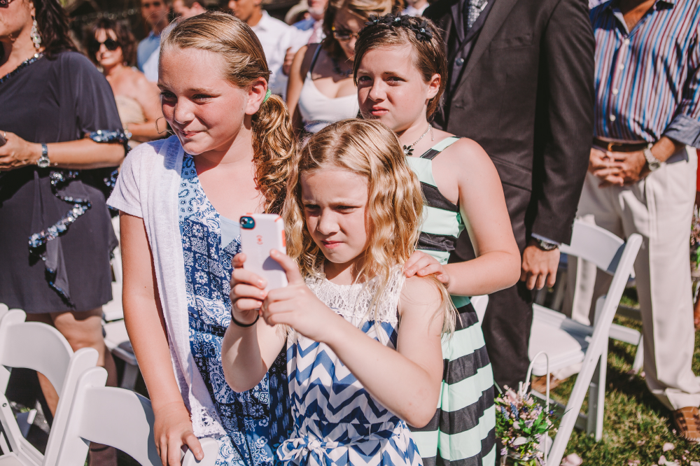 san diego wedding photographer   children in audience with child taking picture on her phone