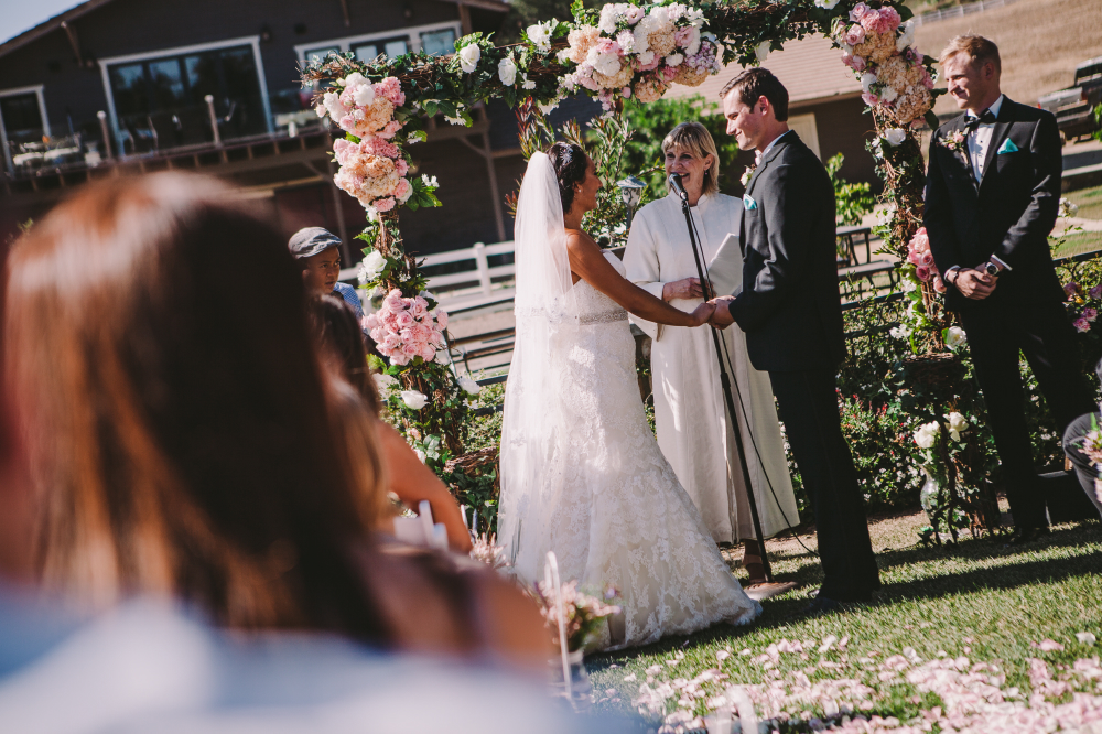 san diego wedding   photographer   tilted view of bride and groom holding hands in front of lady   officiator