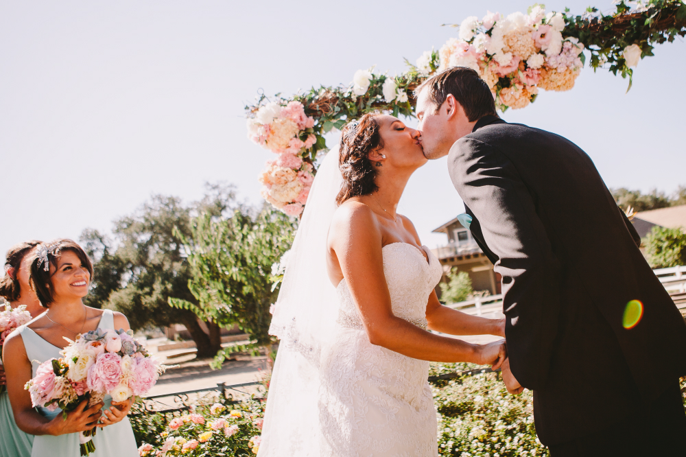 san diego wedding   photographer   tilted shot of bride and groom kissing with bridesmaid smiling   in background