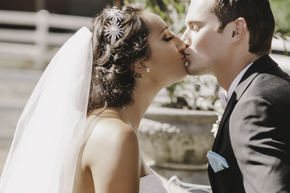 san diego wedding   photographer   closeup of bride and groom kissing with potted plant in   background