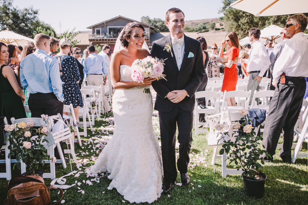 san diego wedding   photographer   newly wed couple walking down aisle smiling holding bouquet