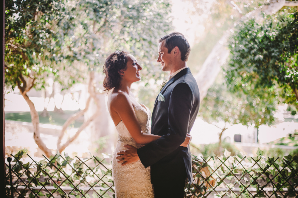 san diego wedding   photographer   bride and groom with cross fence in background