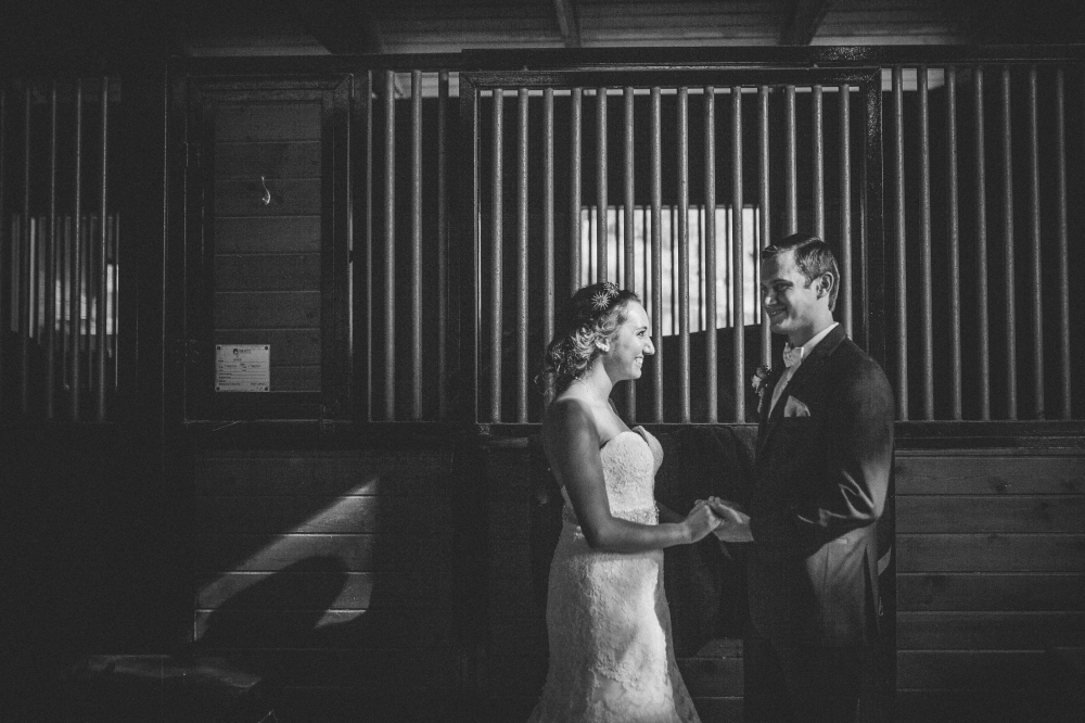 san diego wedding   photographer   monotone shot of newly wed couple in front of stable