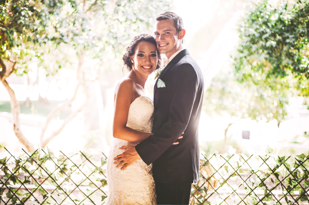 san diego wedding   photographer   newly wed couple holding each other's waist smiling in front   of cross fence